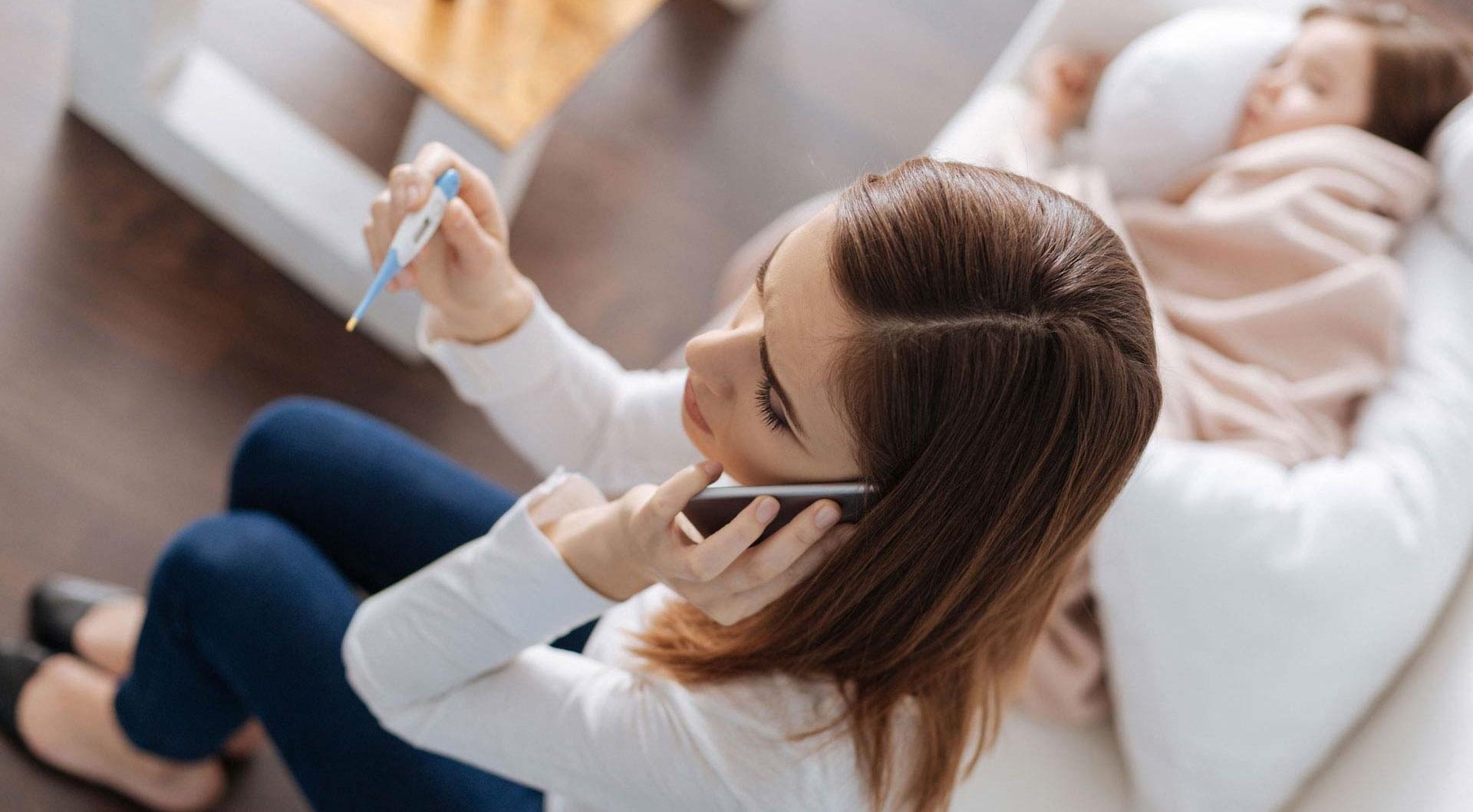 Frau hält Fieberthermometer in der einen Hand und mit der anderen Hand hält sie sich das Telefon ans Ohr.